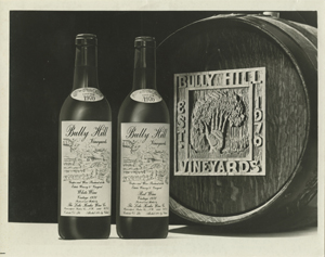Two wine bottles in front of barrel of wine
